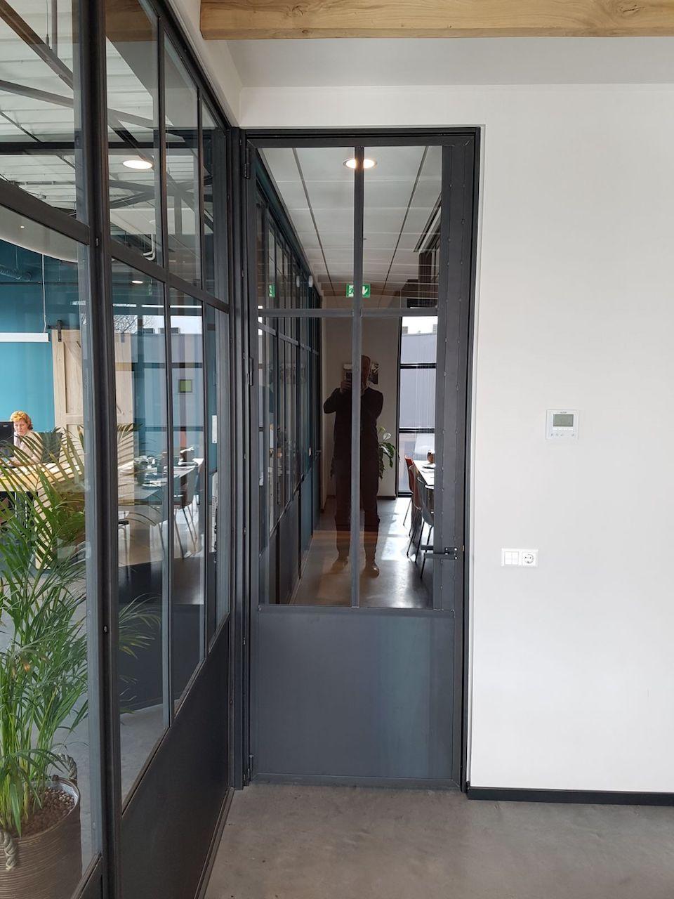 Stalen deur en stalen kozijn bij kantoor interieur