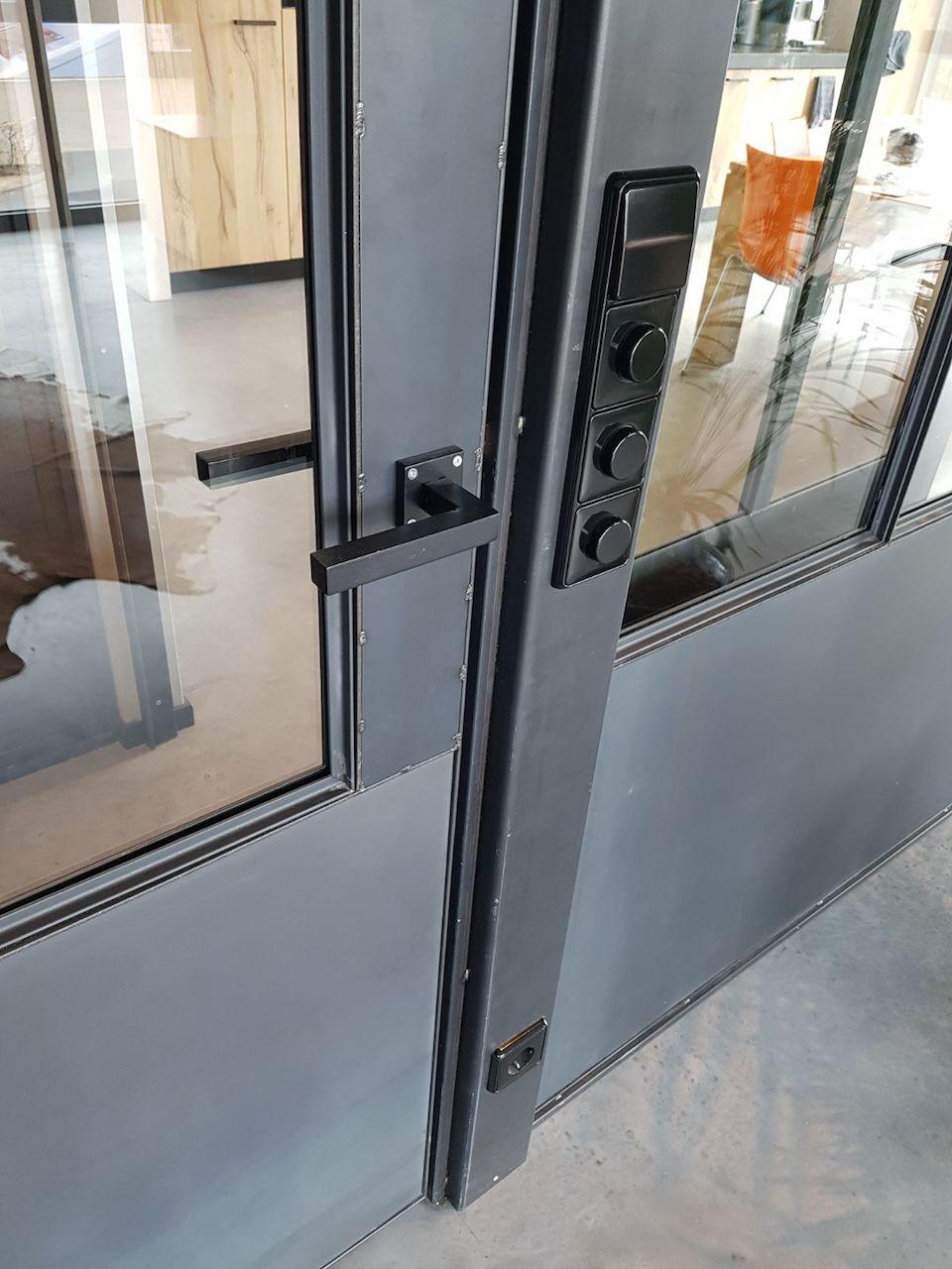 Stalen deur met stalen deurbeslag bij scheidingswand in kantoorruimte