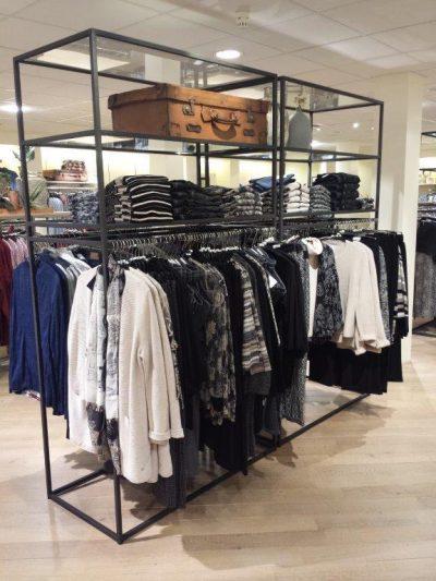 Industriële kledingrekken van staal in winkelinterieur