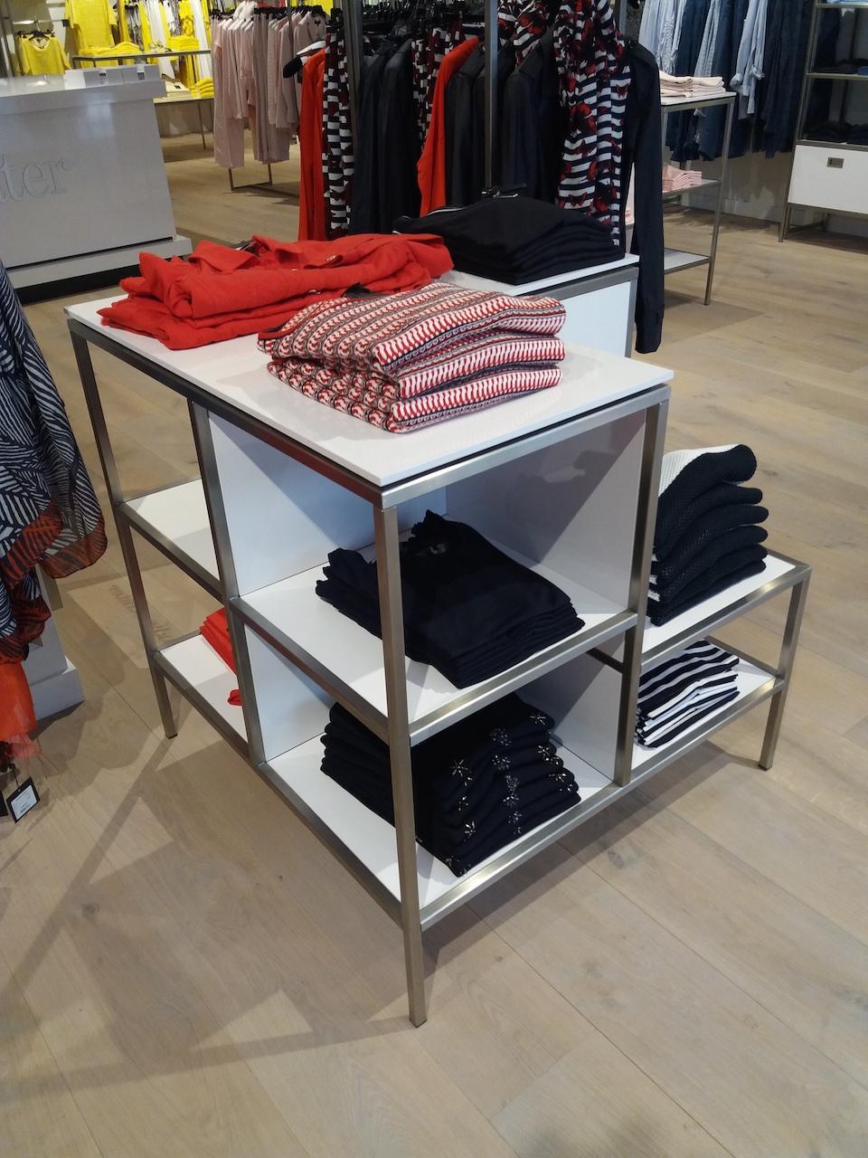 Presentatietafel van rvs en wit hoogglans in kledingwinkel