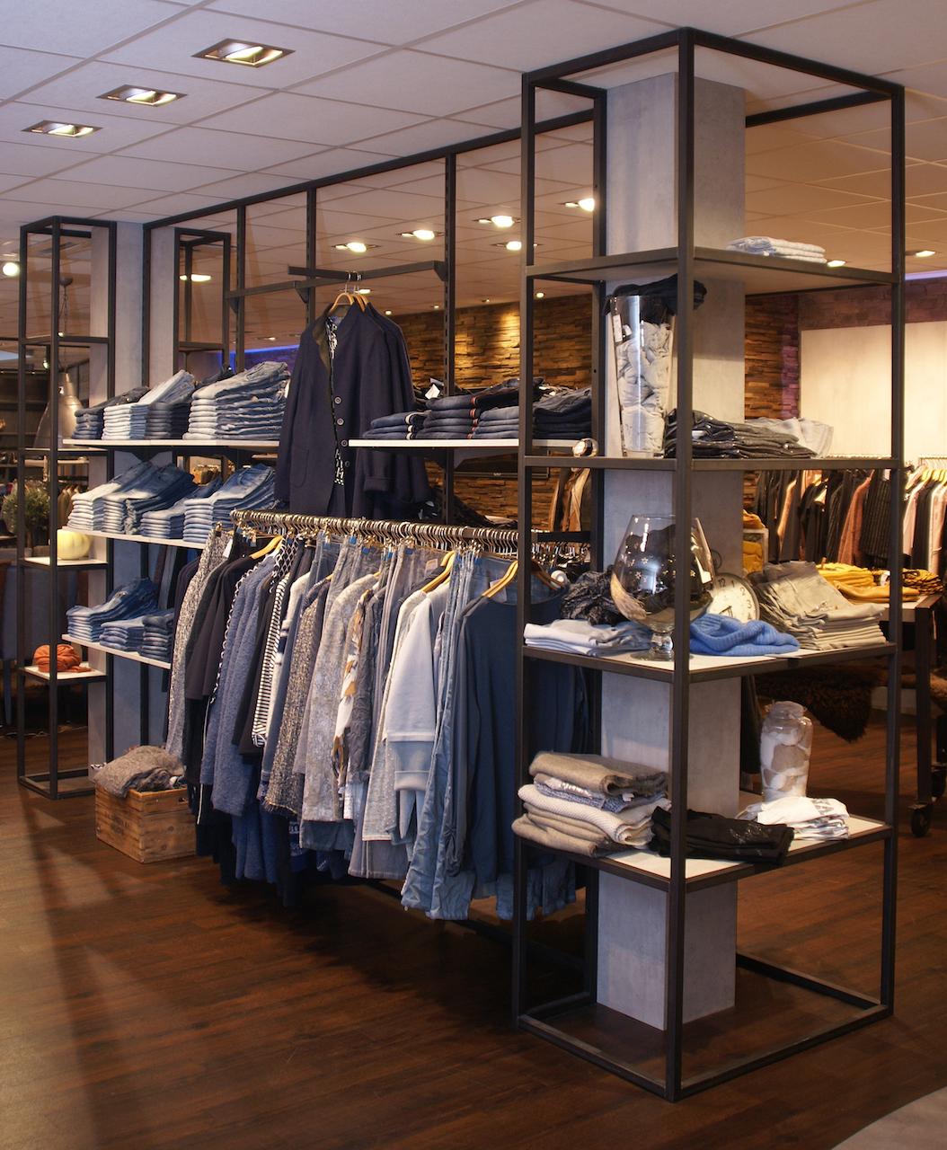 Industrieel winkelinterieur met stalen kledingschappen en stalen kozijn