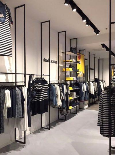 Stalen schappen op maat gemaakt in interieur van kledingwinkel
